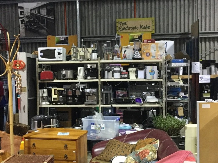 An area of The Recycle Shop with a shelf filled with kitchen appliances such as cookers, a microwave, blenders and more. Above the shelf is a sign on the back wall saying