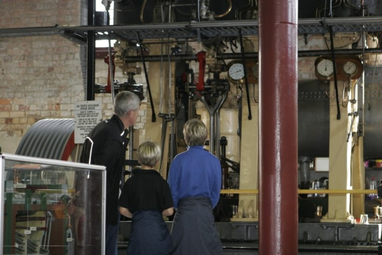 An older man with two boys as they look at old machinery in an engine room at Motat.