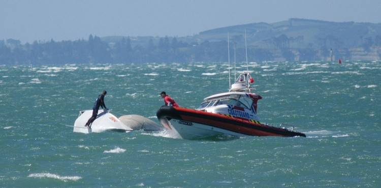 A coastguard boat rescues passengers from a capsized vessel.