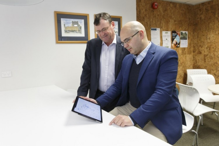 Two men looking at a tablet.
