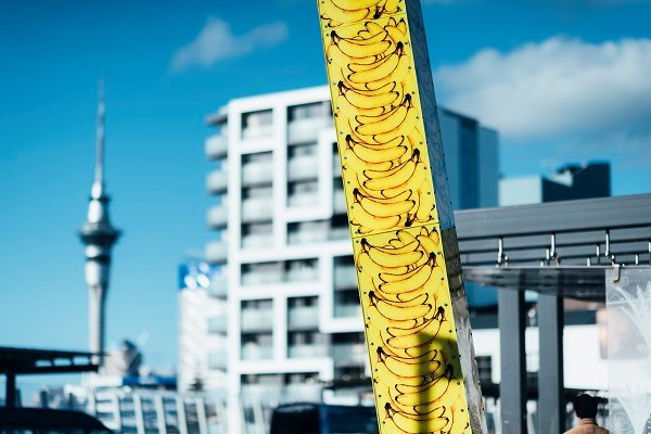 Light sculpture of large pole with bright yellow bananas.
