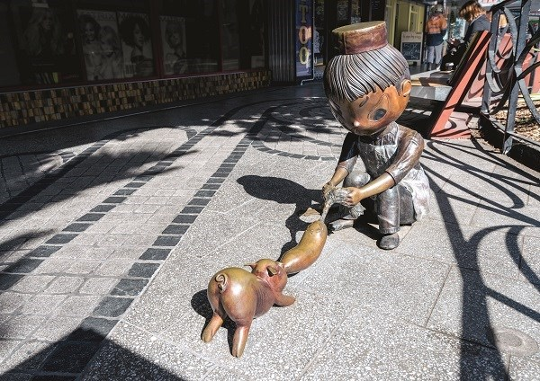 Sculpture of a person fighting with a pig over a sausage.