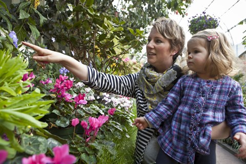 A woman holding a child points at a plant in a greenhouse.